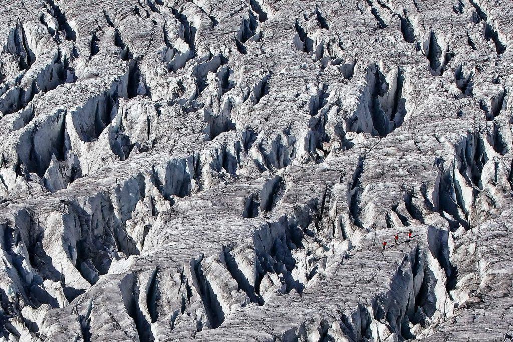 Alpinisti hodaju kroz krajolik ledenjačkih pukotina.