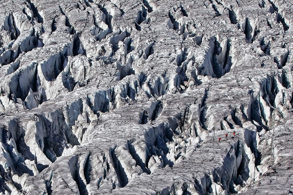 Alpinists walk through the crevasse-landscape