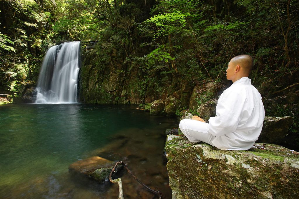 A young monk meditates by the holy waters of Nachi waterfall – one of the holiest places on Kumano Kodo