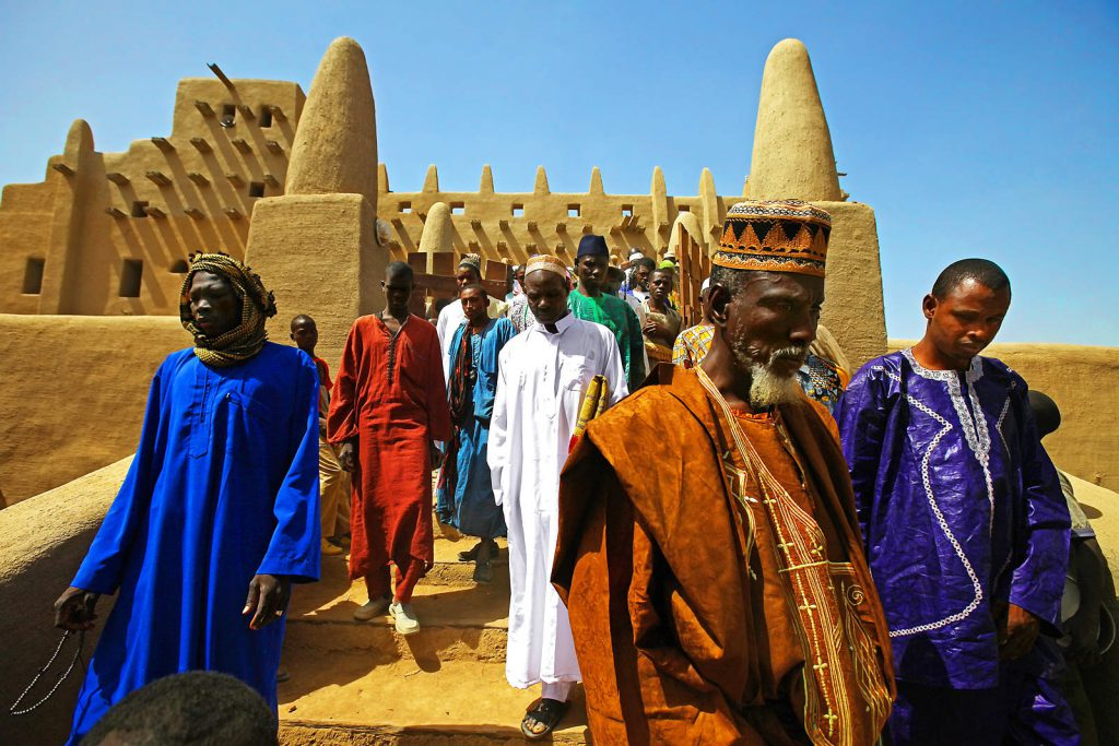 People leaving the Great Mosque in Djenne after a midday prayer