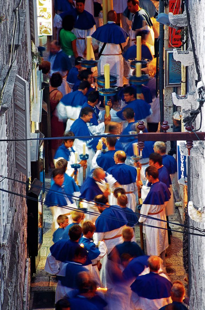 On the day of st. Todor, Korčula's patron saint, all tree fraternities gather and carry their saint's relics through the city's narrow streets. The fraternity of st. Mihovil, whose members are recognized by the blue collars they wear, is known for huge candles carried in the procession by its participants.