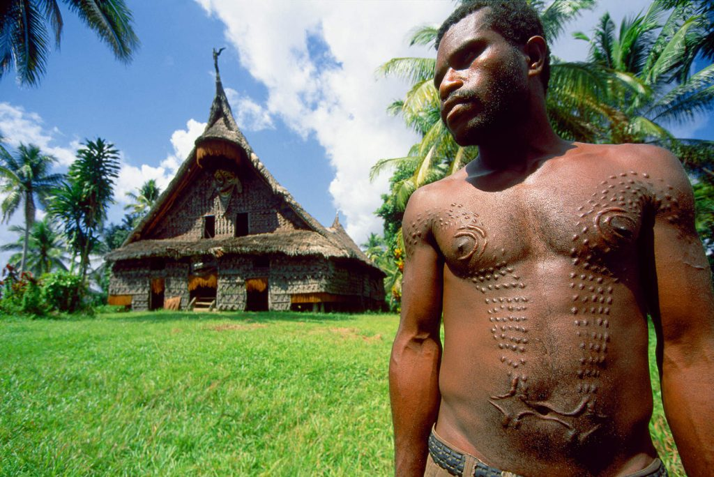 "Men in the swampy region around the Sepik worship crocodiles as part of their crocodile cult. They often gather in big ""spirit houses"" where, among other things, the initiation rites are held. To become men, young boys undergo scarification of their chests and skin. Patterns of scars are made to form the face of a crocodile - a king of swamp – on their bodies."