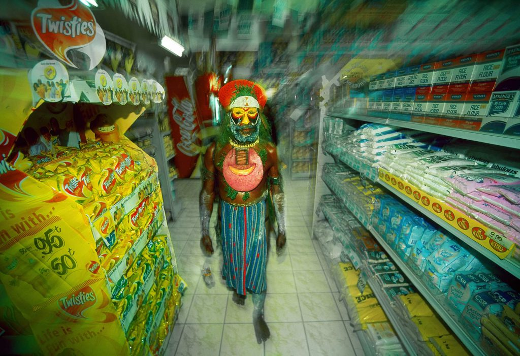 Collision of worlds. Tribal bigmen go shopping in the supermarket.